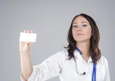 Ritratto del dottore femminile medico Presenting e mostrare carta bianca Fotografia Stock Libera da Diritti