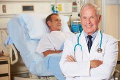 Ritratto del dottore With Patient In Background Immagini Stock