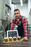 Ritratto del fabbricante di birra con quattro vetri della birra del mestiere sulla tavola Fotografia Stock