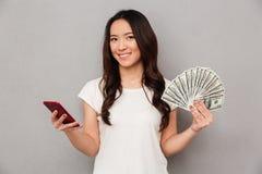 Ritratto del fan castana asiatico della tenuta della donna 20s del dollaro dei soldi Immagine Stock