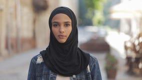 Ritratto del foulard d'uso del hijab della bella giovane donna musulmana che sorride nella condizione della macchina fotografica  video d archivio