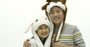 Ritratto del fratello asiatico e della sorella che giocano cappello operato insieme al fronte di sorriso stock footage