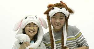 Ritratto del fratello asiatico e della sorella che giocano cappello operato insieme al fronte di sorriso archivi video