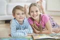 Ritratto del fratello e della sorella felici con i libri di storia mentre trovandosi sul pavimento Immagine Stock