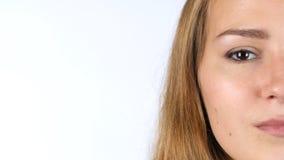 Ritratto del fronte a metà femminile che esamina macchina fotografica, fondo bianco Fotografia Stock Libera da Diritti