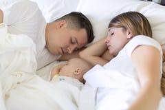 Ritratto del genitore con il suo bambino di 3 mesi nel sonno della camera da letto immagini stock libere da diritti