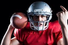 Ritratto del giocatore di football americano che gesturing mentre tenendo palla Fotografia Stock