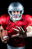 Ritratto del giocatore di football americano che gesturing mentre tenendo palla Fotografie Stock Libere da Diritti