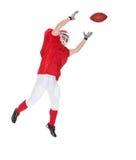 Ritratto del giocatore di football americano che prende una palla immagine stock