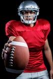 Ritratto del giocatore di football americano risoluto che mostra palla fotografia stock