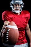Ritratto del giocatore di football americano serio che mostra palla immagine stock