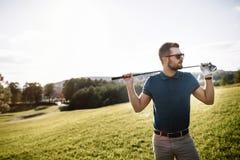 Ritratto del giocatore di golf alla moda in vetri che stanno sui wi del campo da golf Immagini Stock