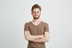 Ritratto del giovane allegro felice con la barba che sorride esaminando macchina fotografica con le armi attraversate sopra fondo Immagine Stock