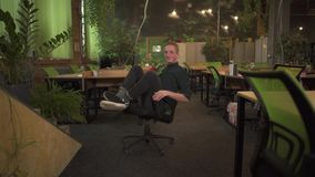 Ritratto del giovane allegro in vetri che filano su una sedia dell'ufficio in ufficio moderno decorato nei toni verdi ufficio stock footage