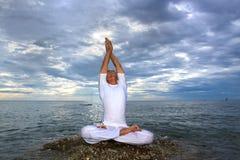 Ritratto del giovane asiatico che fa yoga sulla pietra Fotografie Stock