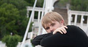 Ritratto del giovane attraente all'aperto, esaminante macchina fotografica Fotografia Stock