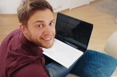 Ritratto del giovane attraente con il computer portatile sul sofà a casa Fotografie Stock Libere da Diritti
