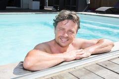 Ritratto del giovane attraente sul bordo della piscina domestica Immagine Stock