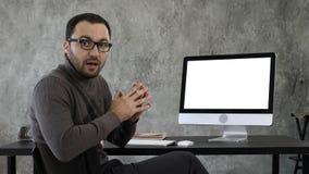 Ritratto del giovane bello in casuale nell'ufficio che parla con macchina fotografica che spiega qualcosa vicino allo schermo bia immagine stock