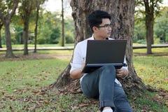 Ritratto del giovane bello che si siede su un'erba verde con il computer portatile nel parco Fotografie Stock