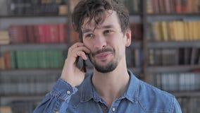 Ritratto del giovane casuale che parla sul telefono video d archivio