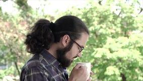 Ritratto del giovane che gode dell'odore da una tazza di caffè Movimento lento stock footage