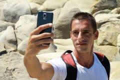 Ritratto del giovane che prende selfie dalla cellula, telefono cellulare, smartphone sopra sulla montagna Fotografia Stock Libera da Diritti