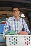 Ritratto del giovane con gli elementi del dormitorio dell'istituto universitario dietro all'automobile, esaminante macchina fotogr Immagine Stock