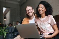 Ritratto del giovane e della ragazza che si siedono nel ristorante e che guardano felicemente in camera con il computer portatile immagine stock libera da diritti