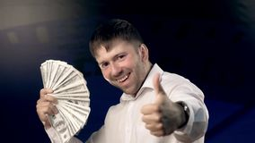 Ritratto del giovane emozionante che ondeggia molti soldi e che mostra le sue emozioni alla macchina fotografica video d archivio