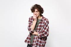 Ritratto del giovane insoddisfatto nervoso in abbigliamento casual che guarda macchina fotografica, chiodi di rosicchiamento isol fotografie stock libere da diritti