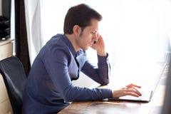 Ritratto del giovane serio sulla telefonata con il computer portatile Immagini Stock Libere da Diritti