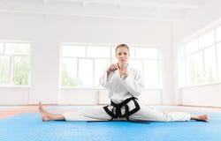 Ritratto del grado della cintura nera della ragazza di karatè, allungante le sue gambe prima dell'addestramento duro fotografie stock libere da diritti