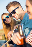Ritratto del gruppo di amici che giocano chitarra e che bevono birra Immagini Stock Libere da Diritti