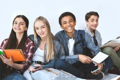ritratto del gruppo multietnico di studenti sorridenti con i taccuini ed i dispositivi digitali immagine stock libera da diritti
