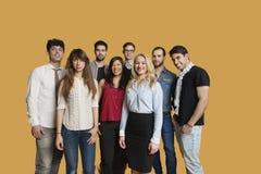 Ritratto del gruppo multietnico felice di amici che stanno insieme sopra il fondo colorato Fotografia Stock