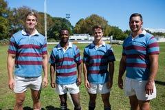 Ritratto del gruppo sorridente di rugby che sta sul campo erboso Fotografie Stock