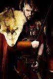 Ritratto del guerriero arrabbiato di vichingo con cuoio, pelliccia e la spada, BO Immagine Stock