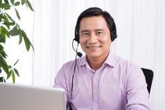 Ritratto del hea d'uso della linea diretta del consulente in materia asiatico bello della persona immagine stock libera da diritti