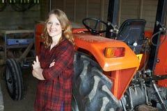 Ritratto del lavoratore agricolo femminile con il trattore Fotografie Stock Libere da Diritti