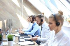 Ritratto del lavoratore della call center accompagnato dal suo gruppo Operatore sorridente del servizio clienti sul lavoro fotografie stock libere da diritti