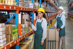 Ritratto del lavoratore femminile del magazzino che sta con il lettore di codici a barre immagine stock