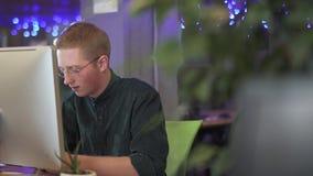 Ritratto del lavoratore maschio creativo occupato che lavora o che chiacchiera sul suo personal computer sui precedenti del eco m archivi video