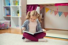 Ritratto del libro di lettura abile della bambina a casa Immagini Stock Libere da Diritti