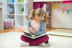Ritratto del libro di lettura abile della bambina a casa Fotografia Stock
