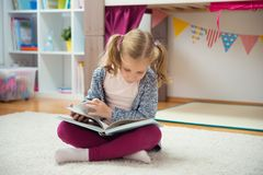 Ritratto del libro di lettura abile della bambina a casa Fotografie Stock Libere da Diritti