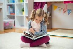 Ritratto del libro di lettura abile della bambina a casa Fotografie Stock
