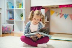 Ritratto del libro di lettura abile della bambina a casa Fotografia Stock Libera da Diritti