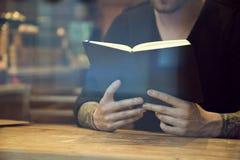 Ritratto del libro di lettura bianco bello dell'uomo dei pantaloni a vita bassa in caffè Fotografia Stock Libera da Diritti