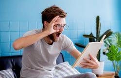 Ritratto del libro di lettura casuale stupito dell'uomo Fotografie Stock